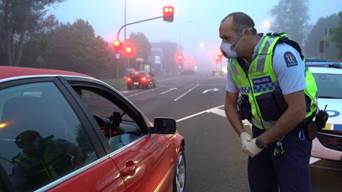A police officer wears Personal Protective Equipment at a checkpoint in Auckland.